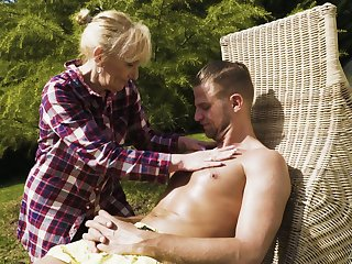 Sexually charged granny Nanney gives a blowjob to young dude in a catch garden